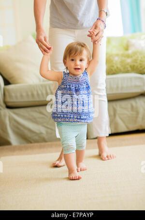 Aider la mère fille bébé (18-23 mois) avec ses premiers pas Banque D'Images