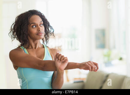 Woman stretching in living room Banque D'Images