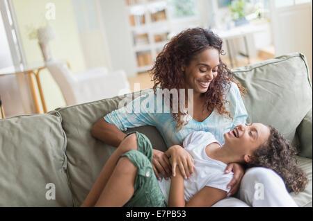 Mère fille tickling (8-9) sur canapé Banque D'Images