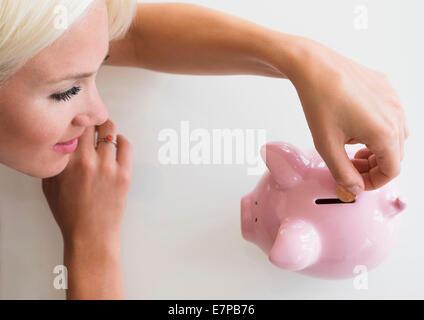 Woman putting coins en piggy bank Banque D'Images