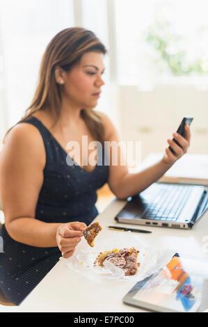 Woman eating croissant et à l'aide de mobile phone in office Banque D'Images
