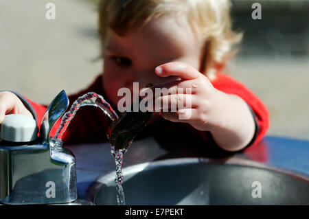 Un jeune garçon (2 1/2 ans) jouant avec une fontaine d'eau Banque D'Images