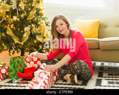 Young woman wrapping presents next to Christmas Tree
