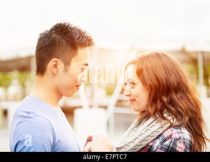 Jeune couple interracial romantique tenant la main et se regardant à l'extérieur dans la lumière au coucher du soleil