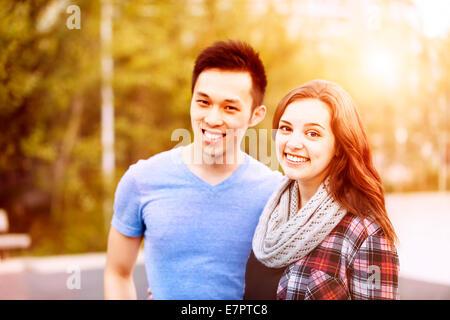 Jeune couple interracial Romantique ensemble et permanent à la caméra à l'extérieur dans la lumière au coucher du Banque D'Images