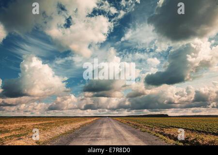 Route de campagne vide dramatique avec ciel nuageux. Effet tonique Vintage Banque D'Images