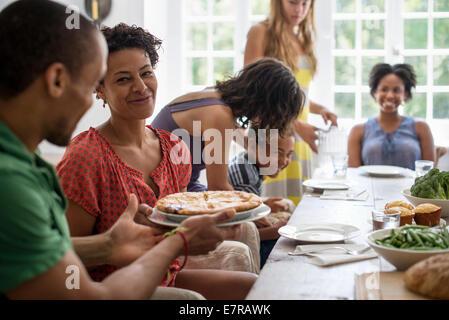 Une réunion de famille, hommes, femmes et enfants autour d'une table à manger partager un repas. Banque D'Images