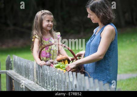 Mère et fille debout dans un jardin avec un panier de légumes. Banque D'Images