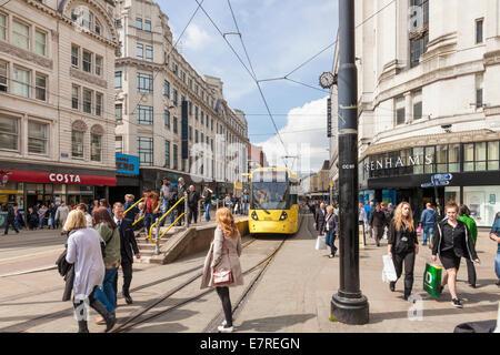 Les gens shopping et tramway Metrolink sur l'animée rue du marché dans le centre-ville de Manchester, Angleterre, Banque D'Images