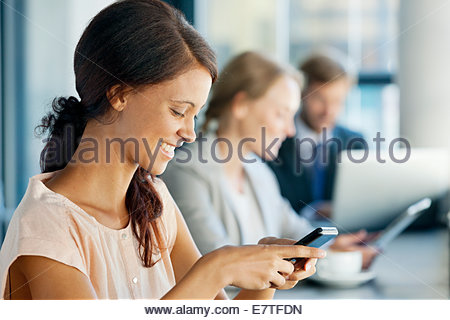 Smiling businesswoman texting on cell phone in coffee shop Banque D'Images
