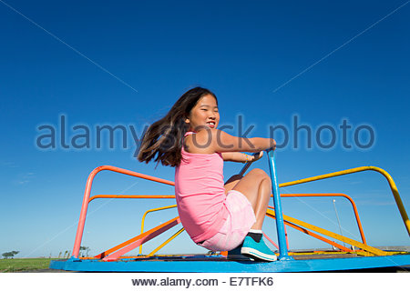 Smiling girl riding carousel in park Banque D'Images