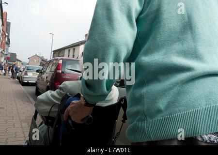 Homme âgé poussant a senior woman dans un fauteuil roulant le long d'une rue Hay-on-Wye, au Pays de Galles UK KATHY Banque D'Images