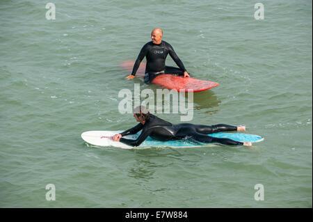 Deux surfeurs à combis en attente sur leurs planches pour une grosse vague / breaker pour surfer sur le long de Banque D'Images