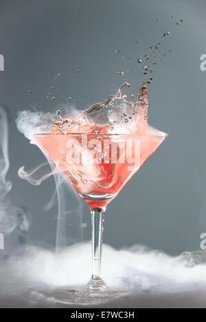 Fumeurs martini cocktail dans un verre conique avec vapeur wafting ou projection de gouttelettes d'une chute spectaculaire de la cerise effe