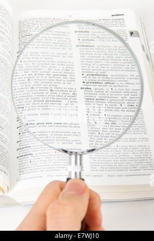 Main tenant un style classique, loupe, à la recherche d'un mot sur la page de dictionnaire, isolé sur fond blanc. Banque D'Images