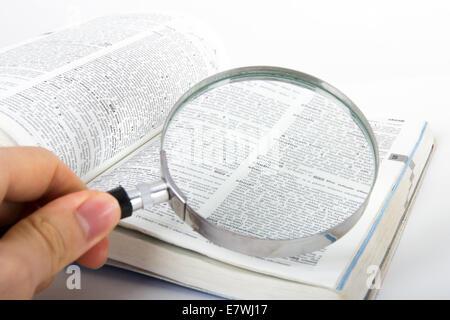 Main tenant un style classique, loupe, à la recherche d'un mot sur Ouvrir un dictionnaire livre, isolé sur fond Banque D'Images