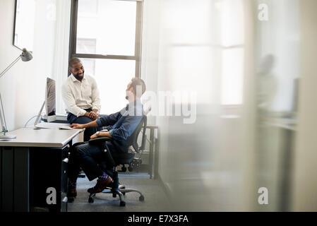 La vie de bureau. Un homme penché en arrière dans une chaise de bureau parlant à un collègue assis sur le bord du Banque D'Images