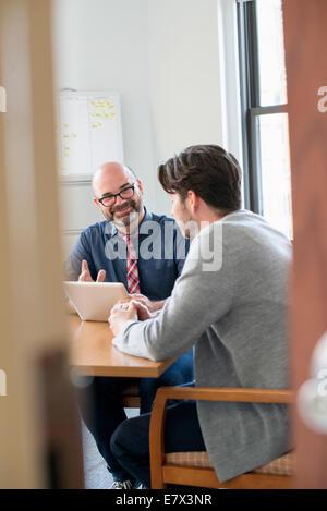 Deux collègues dans un bureau de parler et se référant à une tablette numérique. Banque D'Images