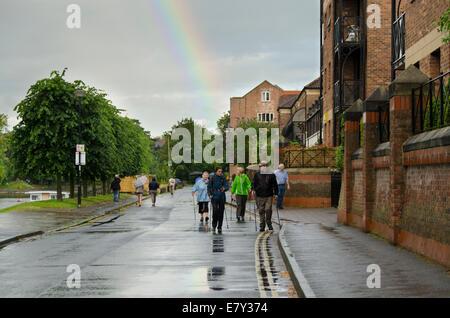En haut arc-en-ciel nuageux gris après une averse soudaine de pluie & wet personnes marchant sur Riverside Road, York, North Yorkshire, Angleterre, Royaume-Uni,