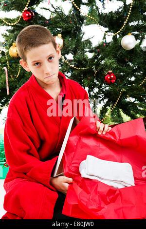 L'ouverture d'un petit garçon enveloppé présente de chaussettes le matin de Noël. Banque D'Images