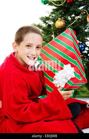 Little Boy shaking a présent le matin de Noël. Banque D'Images