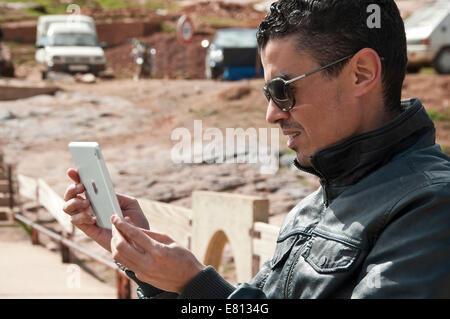 Portrait d'une belle horizontale prise de photos marocain sur une tablette dans le Haut Atlas au Maroc.