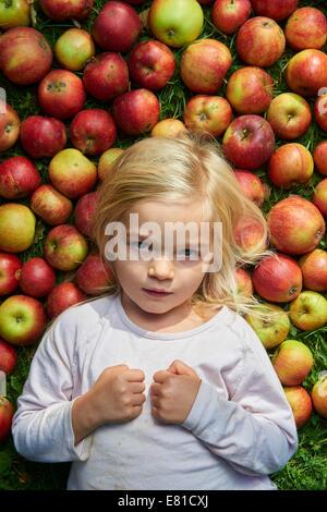 Petite fille couchée sur l'herbe verte avec des pommes rouges Banque D'Images