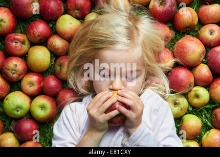 Petite fille couchée sur l'herbe verte pommes rouges Banque D'Images
