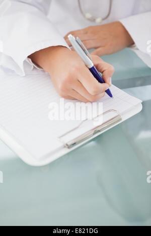 Médecin d'écrire des notes de travail Banque D'Images