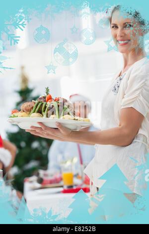 Jolie femme portant poulet rôti à un dîner de Noël Banque D'Images