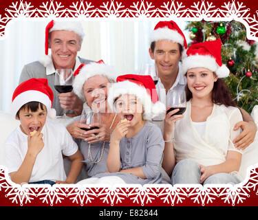 Famille de boire du vin et manger des douceurs à Noël Banque D'Images