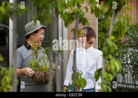 Un homme et une femme debout dans leur jardin. Banque D'Images
