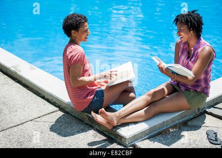 Deux femmes assises à côté d'une piscine, la lecture de livres. Banque D'Images