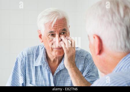 Femme contrôler son visage dans le miroir. Banque D'Images