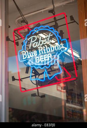 Une enseigne lumineuse pour Pabst Blue Ribbon bière est dans la fenêtre d'une épicerie à New York Banque D'Images