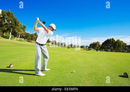 Joueur de golf frappant un coup. Frapper l'homme balle de golf boîte de pièce en T avec chauffeur. Banque D'Images