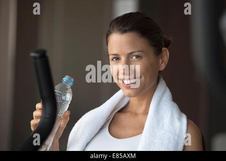 Hydratant femme avec de l'eau embouteillée dans un club de santé Banque D'Images