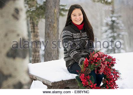 Portrait de fille avec couronne de Noël dans la neige Banque D'Images