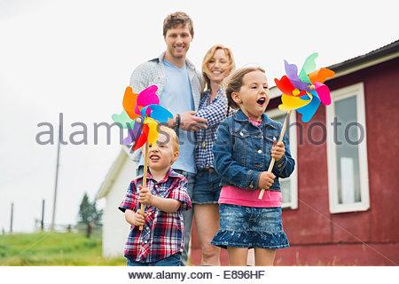 Les parents à regarder les enfants jouer avec pinwheels Banque D'Images