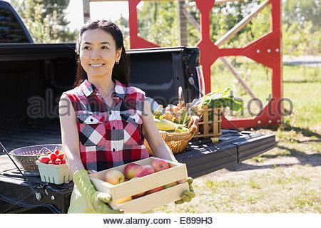 Woman holding caisse de pommes à l'extérieur de chariot Banque D'Images