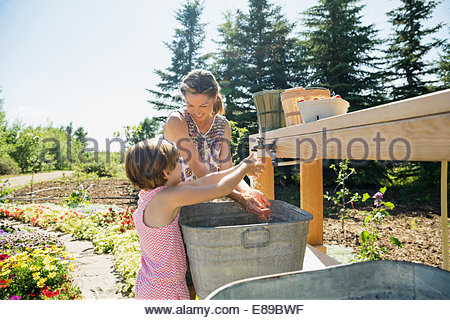 Mère et fille se laver les mains au jardin Banque D'Images
