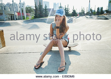 Teenage girl sitting on skateboard à sunny park Banque D'Images