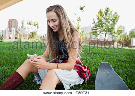 Teenage girl using cell phone in grass Banque D'Images