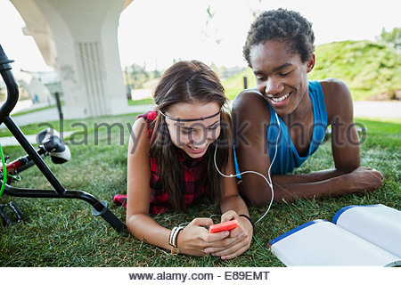 Couple partageant les écouteurs en herbe Banque D'Images