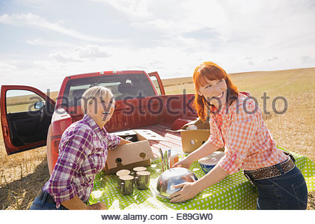 Femmes préparant le déjeuner à sunny crop field Banque D'Images