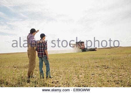 Père et fils regardant combine harvester in field Banque D'Images