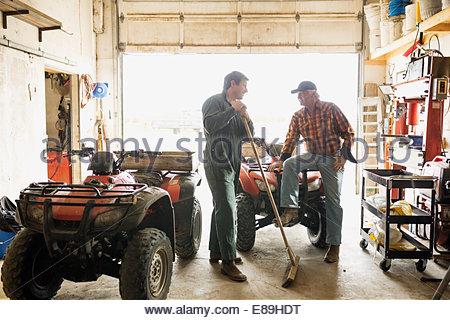 Hommes parler près de quadri motos dans le garage Banque D'Images