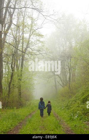Frère et sœur descendre chemin brumeux Banque D'Images