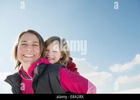 Mother piggyback ride à fille, smiling, Bavière, Allemagne Banque D'Images