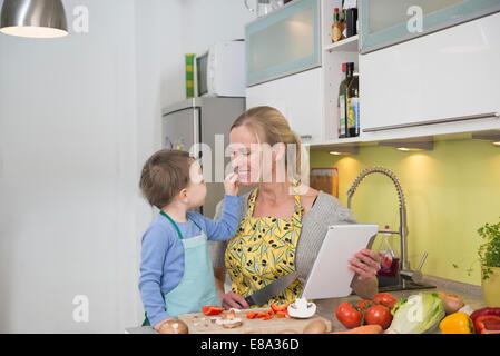 Alimentation garçon sa mère avec des légumes en tranches, smiling Banque D'Images